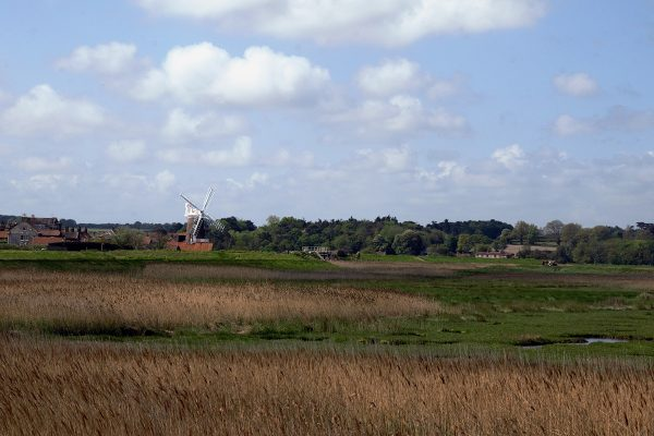 View of an old windmill across the marshes, UK. Norfolk Coast Path. Copyright Stephanie Boon, 2018. All Rights Reserved.