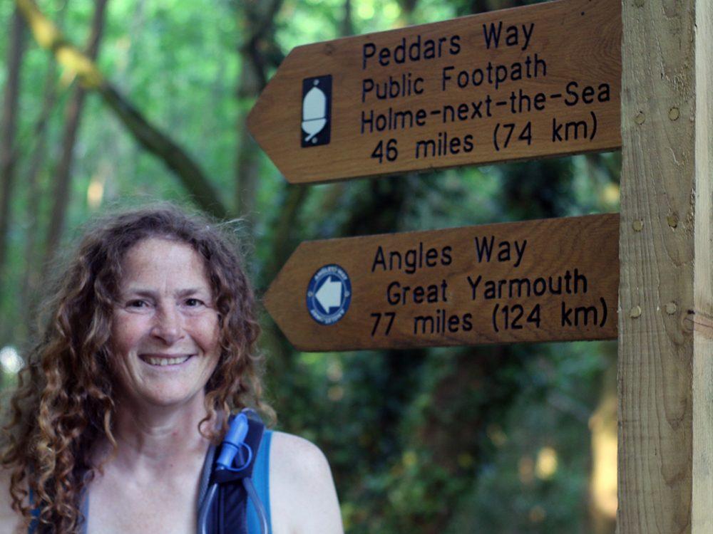 Stephanie Boon standing beside the Peddars Way National Trail sign, Peddars Way, Norfolk UK. Copyright Linda Barlow, 2018.