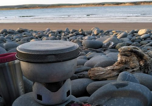 Cooking a wild camp meal on a Trangia on a pebbly beach near Westward Ho! on The South West Coast Path in north Devon, UK. Copyright stephanie Boon, 2018. All Rights Reserved