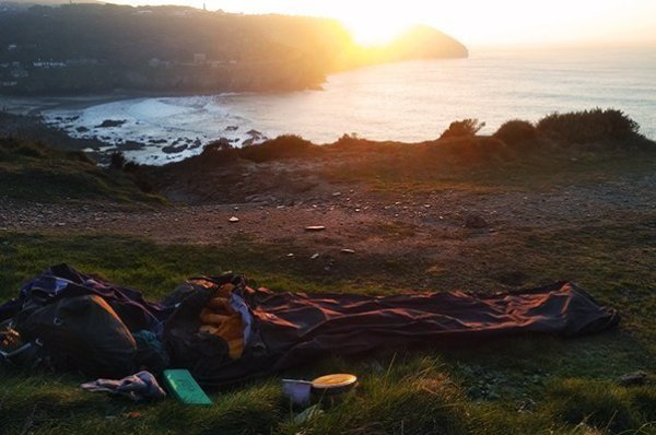 Bivi bag laid out on the ground on the cliff tops at sunset. Cornwall, UK