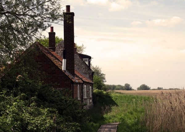 A traditional Norfolk stone building with a very tall chimney (viewed from the gable end) sits on the edge of a marsh. Peddars Way and Norfolk Coast Path National Trail 2018.