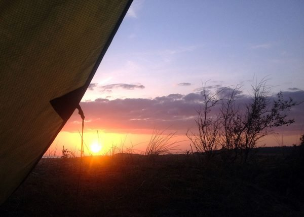 View of a sunset across the dunes on Holkham Beach, with a section of tarp showing. Norfolk Coast Path, 2018