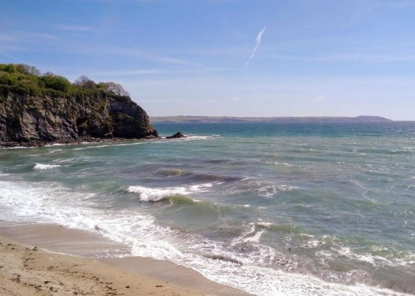 High tide at Porthpean, Cornwall with just a small section of sandy beach.