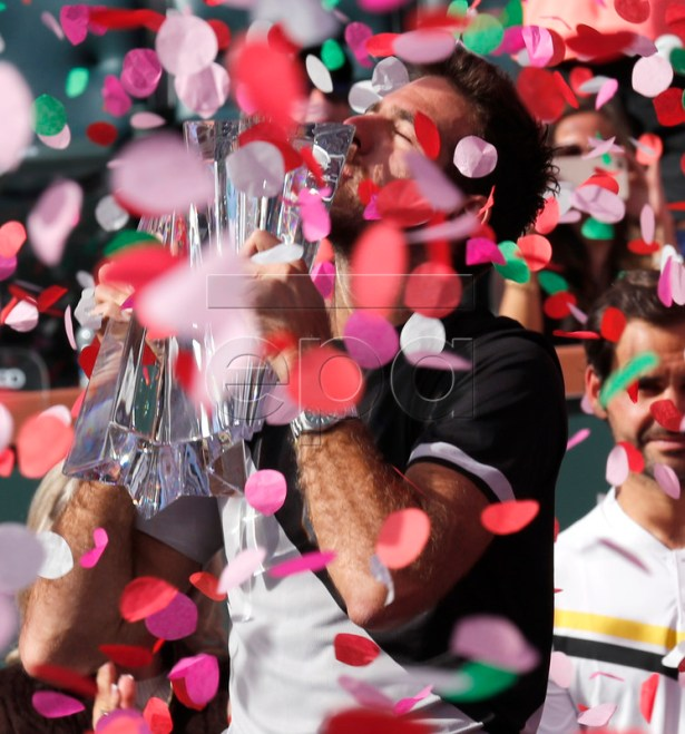Juan Martin Del Potro of Argentina kisses the trophy as confetti falls during the BNP Paribas Open Finals ceremony after defeating Roger Federer of Switzerland at the Indian Wells Tennis Garden in Indian Wells, California, USA, 18 March 2018. EPA-EFE/JOHN G. MABANGLO