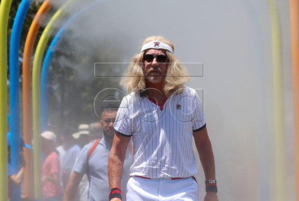 A tennis fan walks through a water spray during day one of the Australian Open Grand Slam tennis tournament in Melbourne, Australia, 14 January 2019.  EPA-EFE/LYNN BOBO
