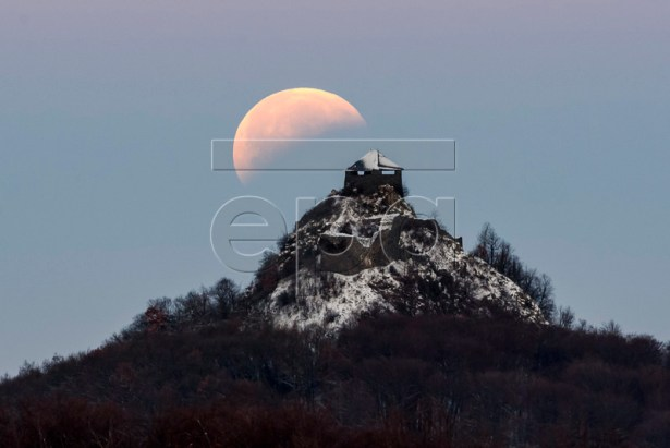 The moon fully shadowed by the Earth is seen above the castle of Salgo during a total lunar eclipse near Salgotarjan, some 109km northeast of Budapest, Hungary, 21 January 2019. The entire eclipse was visible from North and South America, as well as parts of western Europe and north Africa. The phenomenon was referred to by some as a 'super blood wolf moon' being a combination of a 'blood moon' as, during the eclipse, only the sun rays refracted by the earth atmosphere are reflected from the moon surface and give it a reddish color, a 'supermoon' given the large apparent size of the moon due to its relative proximity to earth and finally a 'wolf moon', the name often given to the full moon in January.  EPA-EFE/PETER KOMKA HUNGARY OUT