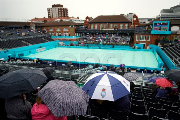 Spectators protect themselves from the rain during the second day of the Fever Tree Championships tennis tournament at Queen's Club in London, Britain, 18 June 2019. EPA-EFE/WILL OLIVER