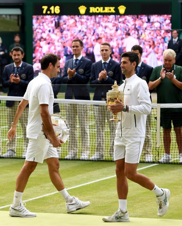 Novak Djokovic (R) of Serbia celebrates with the trophy after winning against Roger Federer (L) of Switzerland during their Men's final match for the Wimbledon Championships at the All England Lawn Tennis Club, in London, Britain, 14 July 2019. EPA-EFE/ANDY RAIN EDITORIAL USE ONLY/NO COMMERCIAL SALES