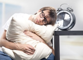 Young needy man hugging his pillow beside a clock
