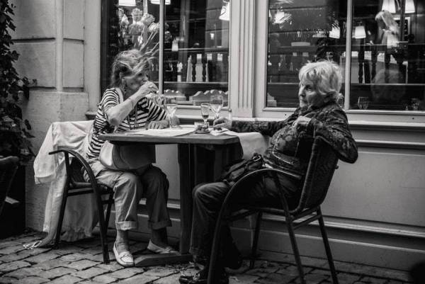 Two older ladies sitting outside eatery having a glass of wine