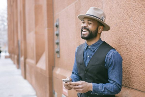 Man with hat laughing holding phone 5 Pros of Long Distance Relationships by Mudabbira Khan