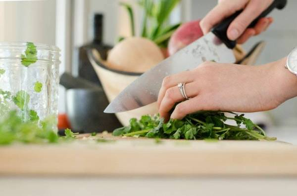 Heat Up The Romance in Your Kitchen woman cutting green leafy herb
