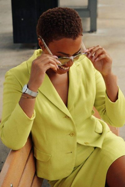 sexy woman holding sunglasses sitting on bench green suit nappy collection pexels