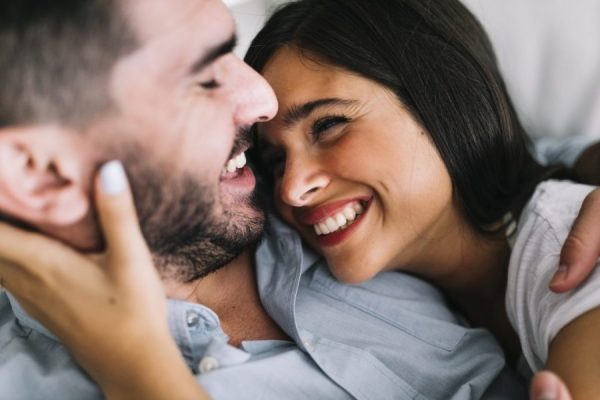 young woman smiling at man cuddling The Most Sensitive Parts of a Man to Get Him in the Mood