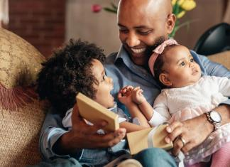man signs a birth certificate young boy smiles at father holding baby sister 1