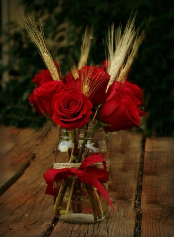 gold candle holders and burgundy flower bouquet in mason jars
