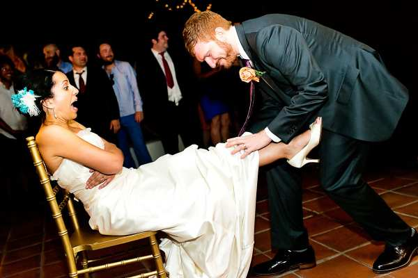 Groom Removes the garter -123WeddingCards