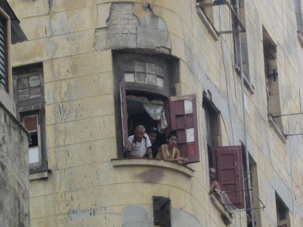 Vecinos atrapados en el edificio en derrumbe observan a través de las ventanas el despliegue policial. (14ymedio)