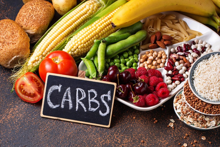 Blackboard with the word 'Carbs' in front of bowls of rice, legumes, tomatoes, corn, bananas, peas, green beans, almonds, cherries and raspberries