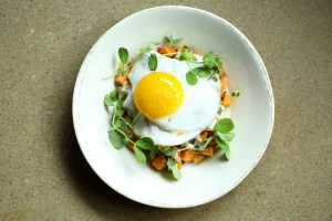 A brunch favorite, duck egg hash is a savory combination of duck leg confit, sweet potatoes, arugula and bearnaise aioli topped with a sunnyside up duck egg.