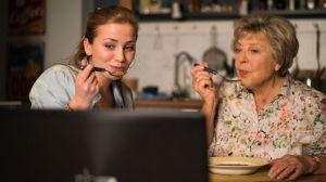 """Ehrgeizig: Ihrer Enkelin Lea (Anna Sophia Claus) zuliebe isst Helga Beimer (Marie-Luise Marjan, r.) gemeinsam mit ihr live vor der Kamera. Lea ist überzeugt, dass sie mit dem in Süd-Korea gehypten """"Mukbang"""" auch hierzulande Erfolg haben wird."""