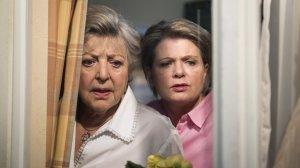 Helga (Marie-Luise Marjan, l.) und Gaby (Andrea Spatzek) entdecken einen Umzugswagen vor dem Nachbarhaus. Gibt es eine Verbindung zu der Infoveranstaltung, die am Abend im 'Akropolis' stattfindet? Darin soll es um ein geheimnisvolles Bauvorhaben in der Lindenstraße gehen…