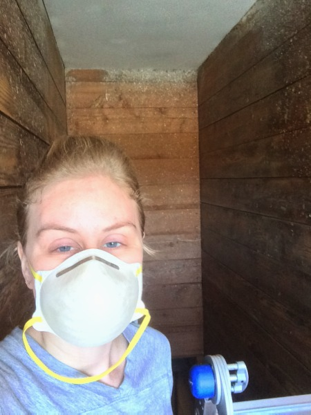 Prepping original shiplap by sanding the walls before paint is applied