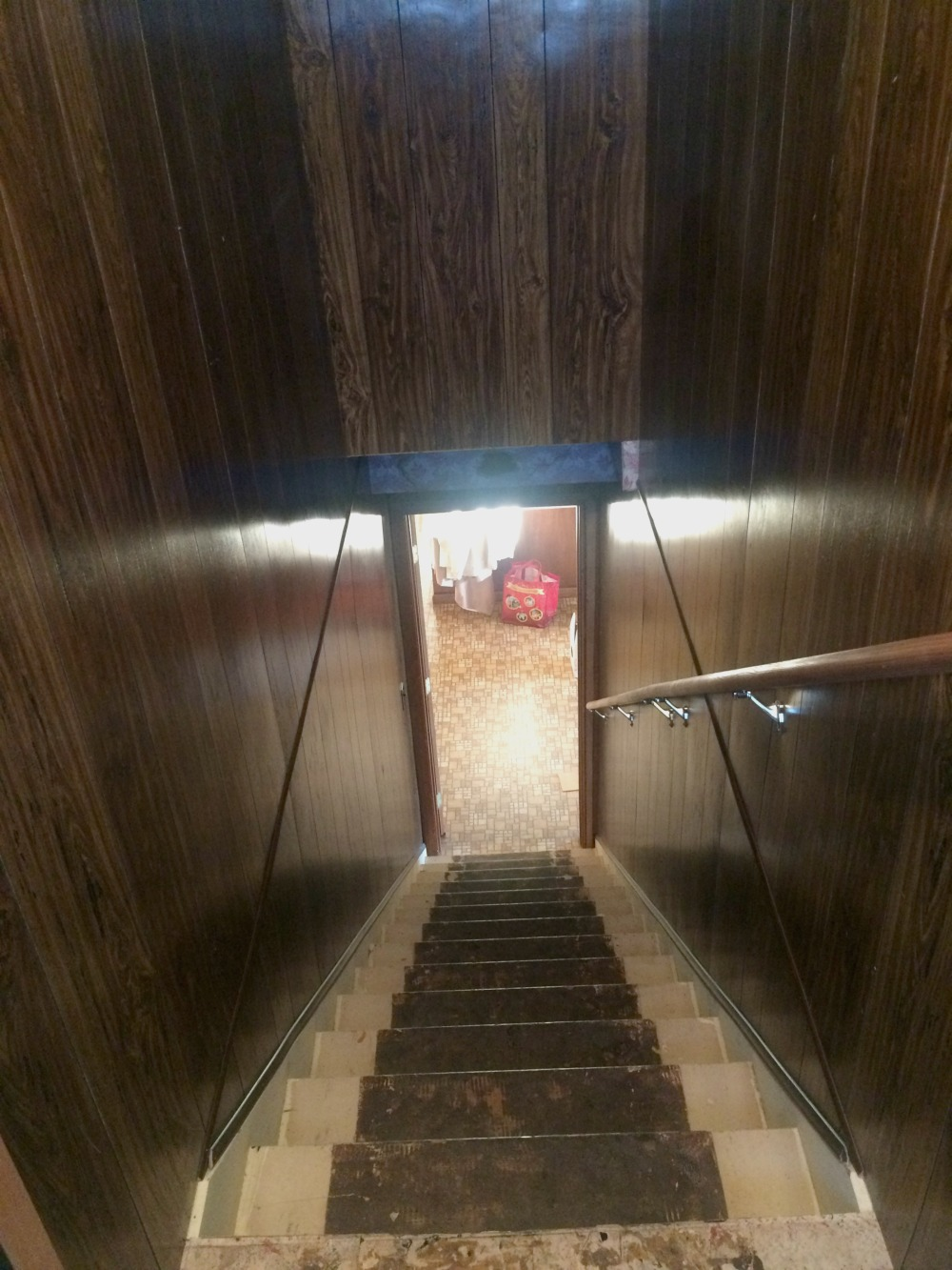 A view down a stairwell with dark wood paneling