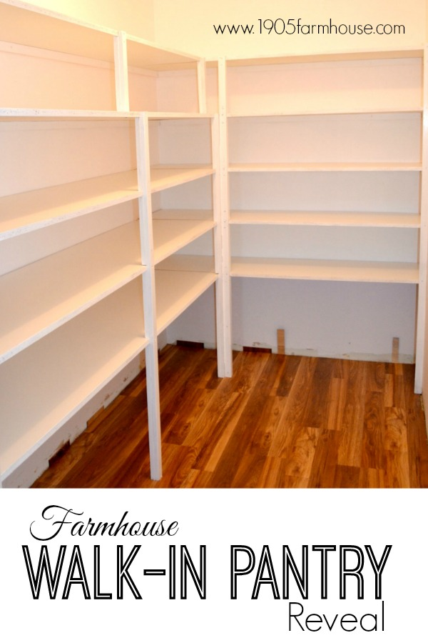 White shelves along two walls with a laminate wood floor in a walk-in pantry