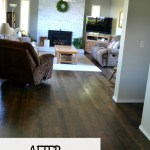 A wide angle shot of a living room after laminate flooring was removed and the original hardwood was refinished