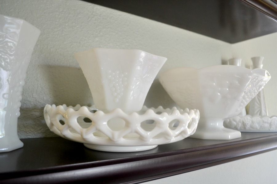 Milk glass is displayed on open shelving in a living room