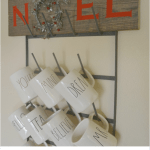 The letters N, E, L with a silver wreath as the O to spell out NOEL on a wood board hung on a mug rack with Rae Dunn mugs hanging below