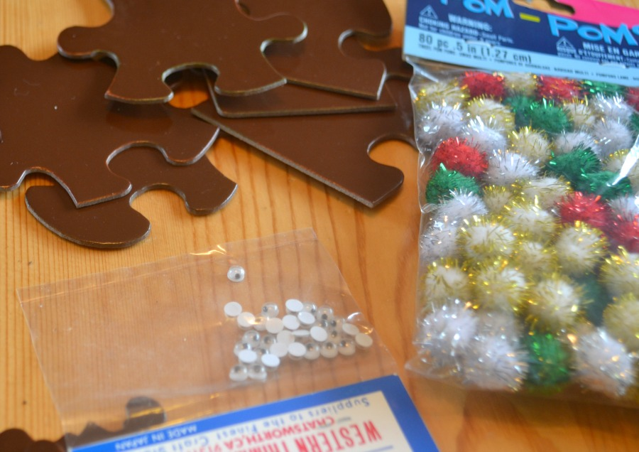 The supplies you need for puzzle piece reindeer includes craft eyes and pom poms
