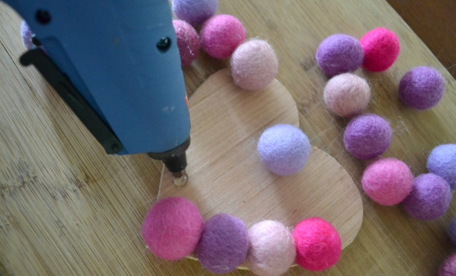 Use a glue gun to apply the felt balls to the wood base