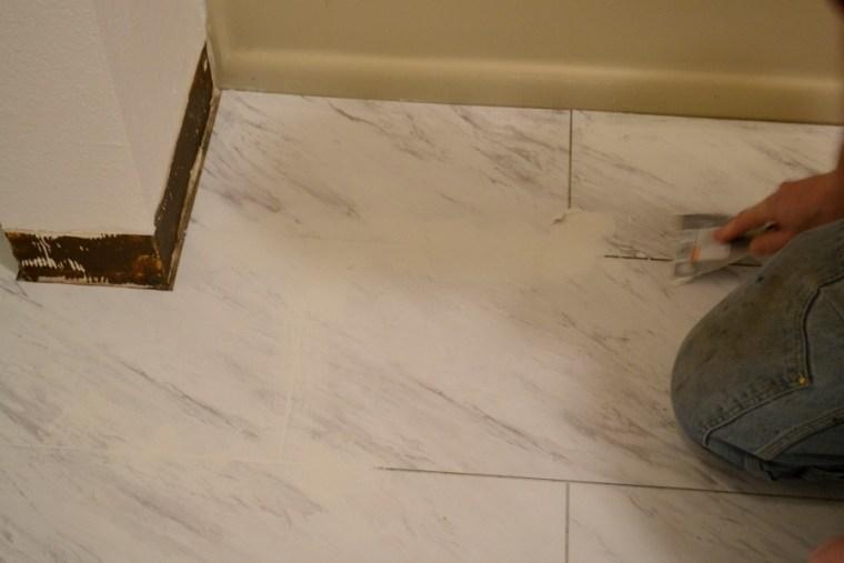 Applying grout to carerra marble tiled floor