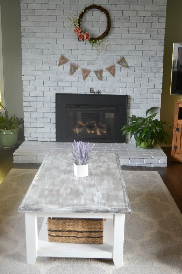 An outdate coffee table updated with milk paint and a dry brush technique to acheive a farmhouse look