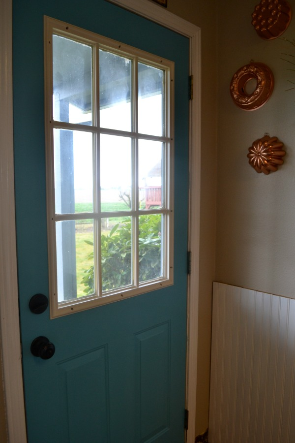 A beautiful aqua blue metal door that brightens up the laundry room