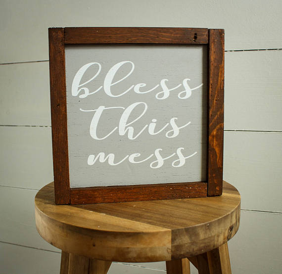 """Wood framed sign sitting on a stool with a gray background that says """"Bless This Mess"""""""