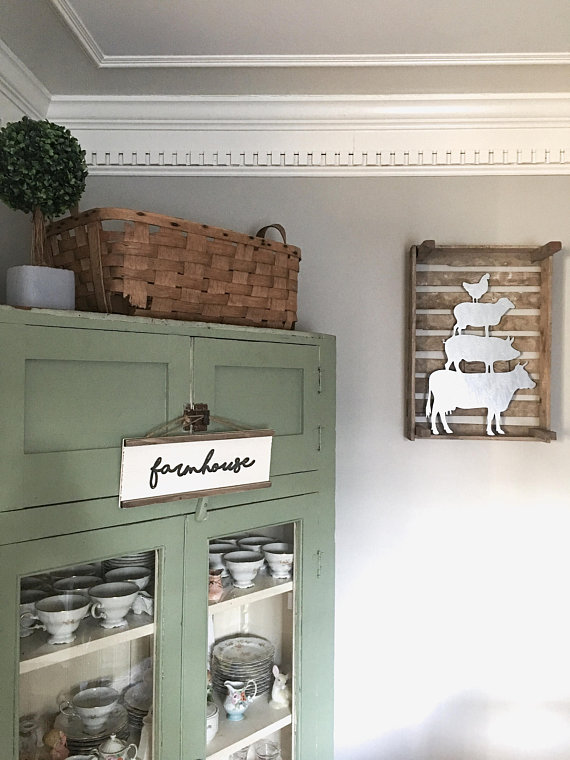 A corner view of a room with a hutch on the left and a metal cut out of a cow, pig, sheep and chicken stacked up
