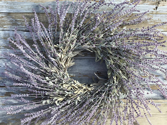 A Lavendar wreath that feathers out on a wood background