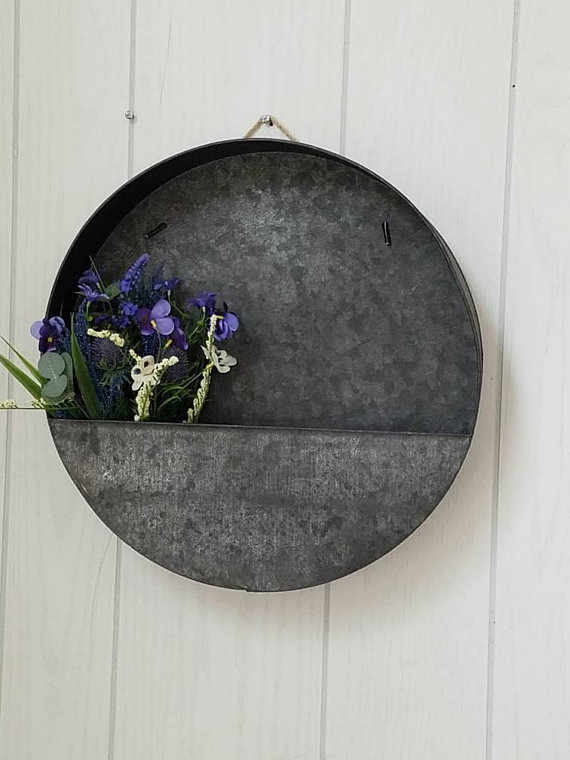 A circle wall pocket made of metal and holding flowers