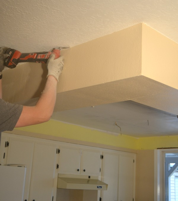 A man using a multi-tool to cut around the top of a drop ceiling
