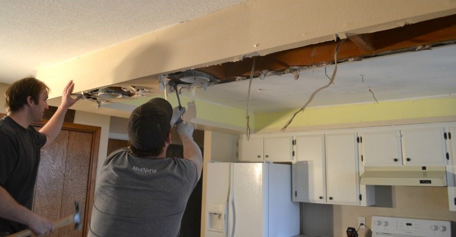A man demoing drywall with a hammer in a drop ceiling frame