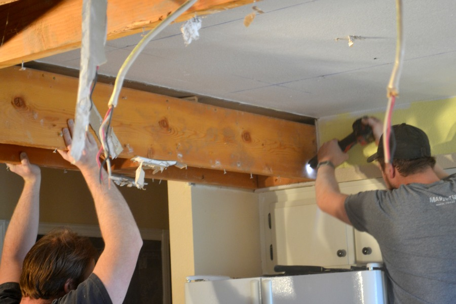 Two men removing a wood frame drop ceiling, one man holding the frame while the other cuts nails