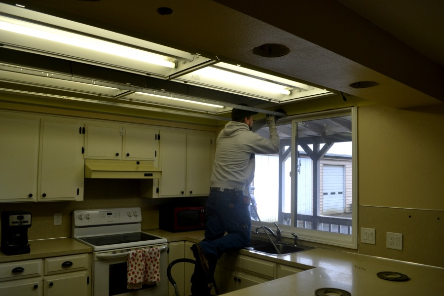 A man working on remove a metal frame that contained fluorescent kitchen lights