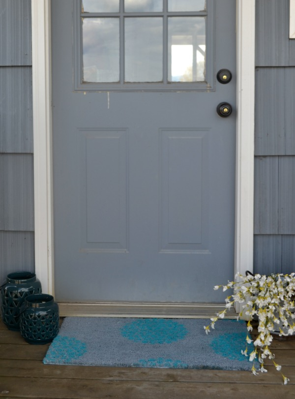 Completed gray and aqua rug placed next to a door with lanterns and flowers on the sides
