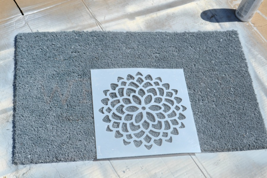 Gray spray painted welcome mat with a white mum stencil laid on top