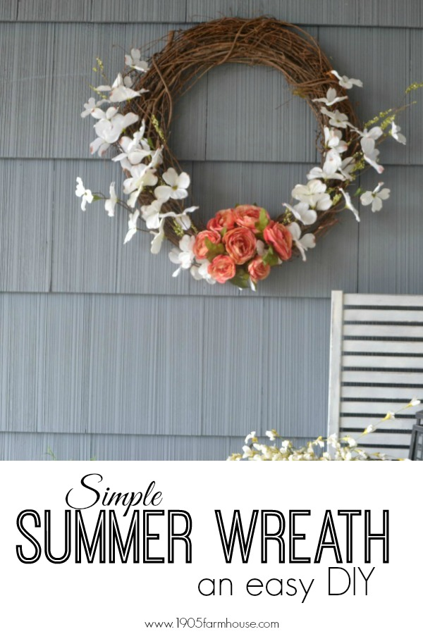 A grapevine wreath with pink roses and white magnolia faux flowers on a blue house