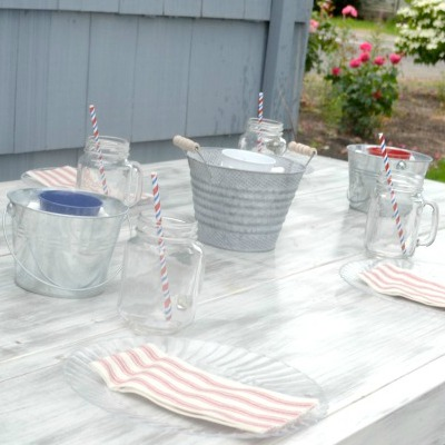 A side view of a table set with place settings and metal buckets for a centerpiece