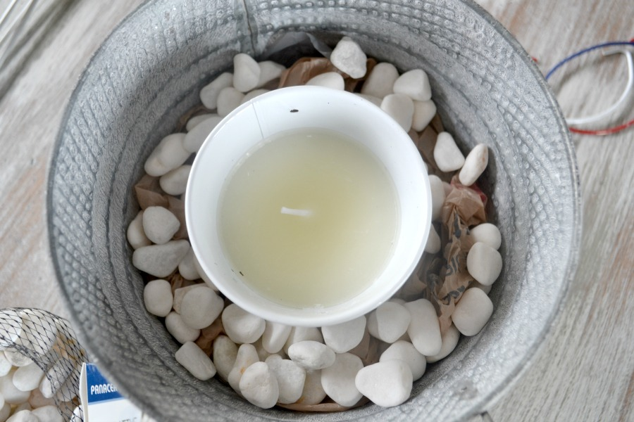 An above view of a candle in a bucket surrounded by white filler rocks